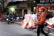 © Licensed to London News Pictures. 30/12/2011. A young man carries goods for sale through a street in Hanoi,  Vietnam. Photo credit : Stephen Simpson/LNP