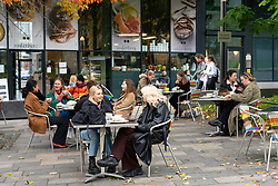 Edinburgh, Scotland, UK. Members of the public sitting outdoors at a cafe near The Meadows in Edinburgh. The Scottish Government covid regulations beginning at 6pm today means cafes and bars in Lothian and the central belt of Scotland  must close for 16 days. Iain Masterton/Alamy Live News