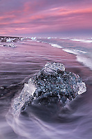 Water pattern caused by incoming wave creates an interesting foreground shape with stranded icebergs at sunset along the beach at Jokulssrlon, Iceland