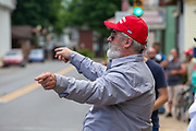 """Watsontown, PA (June 28, 2020) -- A man in a red Make America Great Again cap waves his arms as Black Lives Matter protesters across the street chant """"we love you"""" directed at the counter protesters. About 200 BLM protesters were confronted by nearly 50 counter-protesters who shouted """"all lives matter"""" and called them communists. Local anti-racist activist group """"If Not Us, Then Who?"""" organized the event."""
