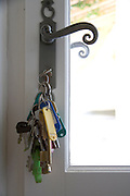 lock of a house door with many keys hanging on a key chain