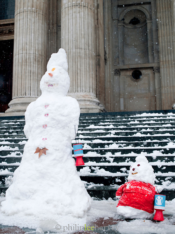Two 'charity' snowmen on the steps of St Pauls Cathedral in London, UK
