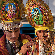 Emotional moment for the bride : she is leaving her childhood home in her village, moving away to her husband's home.  Hats with Hindu deity: Ganesh for the man, Radha Krishna for the woman. Traditional wedding in the Himalaya.