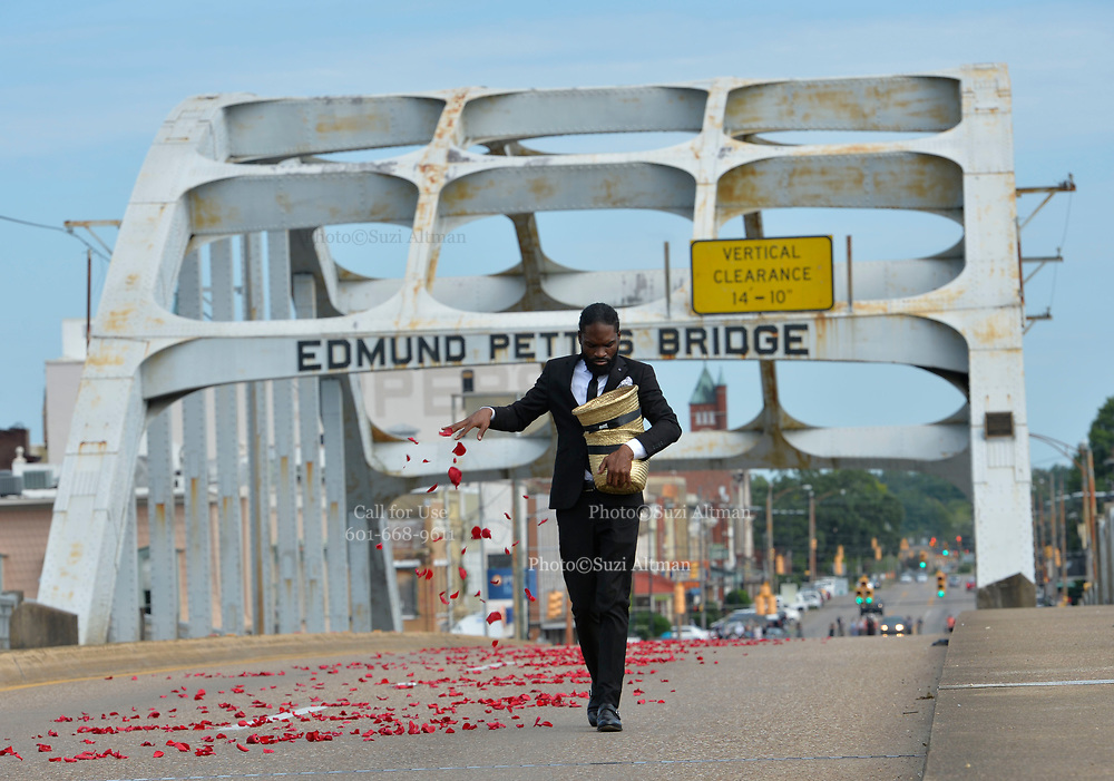 7/26/2020 SELMA/Alabama - Justine Mayes , right and Marcus Sharp spread 3 thousand rose petal along the Edmund Pettus Bridge before the horse drawn carriage with the casket of Civil Rights Icon and Congressmen John Lewis from the horse the horse drawn carriage that just crossed the Edmund Pettus Bridge for the last time into the casket to head to the State Capitol, where he will lay in state.. A horse drawn carriage from Watkins Funeral Home in Atlanta leads the flag draped casket of Civil Rights icon and Congressman John Lewis over the Edmund Pettus Bridge for the last time.The rose petals represent the blood shed from Bloody Sunday in 1965 where Lewis was beaten by police and ended up with a  fractured skull. On the anniversary of President Lyndon Johnson signing the Voting Rights Act, Congressman John Lewis's casket is pulled by a horse drawn carriage  across the Edmund Pettus Bridge in Selma for the last time. The casket is headed to the State Capitol in Montgomery where he will lay in state and then will head to Washington DC and then to his final resting place in Atlanta Georgia.  Photo© Suzi Altman