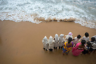 Two teachers stand with a group of girls, all students and from more than one religion, and feel the waves lap their feet at the beach at Galle Face Green in Colombo, Sri Lanka