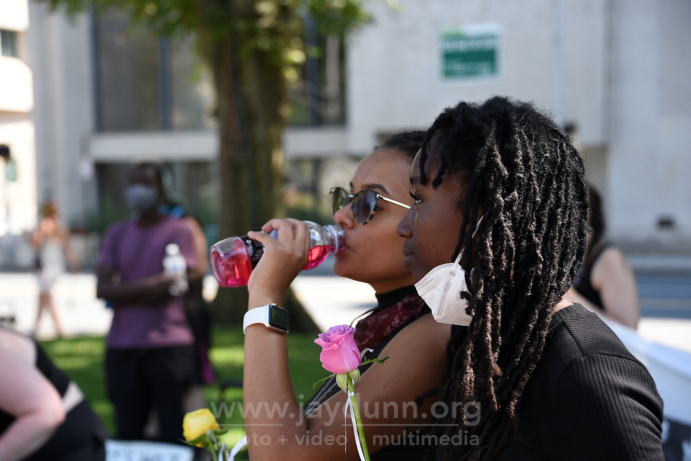 """From left, organizers Clark Atkinson and Hadiyah Sackey listen to a speaker at the event. Determined to keep continuing racial injustice in the public eye, a small but well-organized group of protesters held a July 4th """" March for Liberty and Justice for All"""" in Waterbury, CT,  gracing each individual murdered with roses in an urgent, emotional appeal. Photograph by Jay Dunn."""