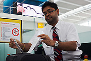 "A No Sharp objects warning is plain to see as a British Airways check-in employee attaches a luggage tag to the suitcase of a Business Class passenger about to take a long-haul flight from London Heathrow Airport's Terminal 5. The bag is about to disappear down the conveyor belt to join up to 70,000 other items during this average day at T5. With a bar code to identify both the bag and its owner's destination as well as the three letter IATA code, the bag enters 11 miles of underground conveyor belts beneath the 400m (a quarter of a mile) length of Terminal 5 at Heathrow Airport. T5 alone has the capacity to serve around 30 million passengers a year and was completed in 2008 at a cost of £4.3bn. From writer Alain de Botton's book project ""A Week at the Airport: A Heathrow Diary"" (2009). ."