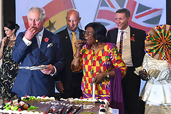 The Prince of Wales eats a birthday cake made for him and other guests, during a reception at the British High Commissioner's residence in Accra, Ghana, on day three of their trip to west Africa.