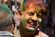 A man with multicoloured paint powder on his face and hair embraces another man in the street during the festival of Holi, in Udaipur, Rajasthan, India