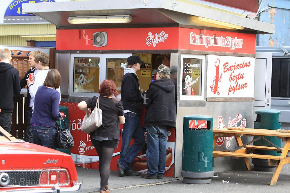 Locals enjoy food from famous hot dog stand, Baejarins Beztu Pylsur, in downtown Reykjavik, Iceland.