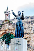 A statue in memory of the Pope John Paul II (Joao Paulo II) the Roman aqueduct in the background Coimbra, Portugal