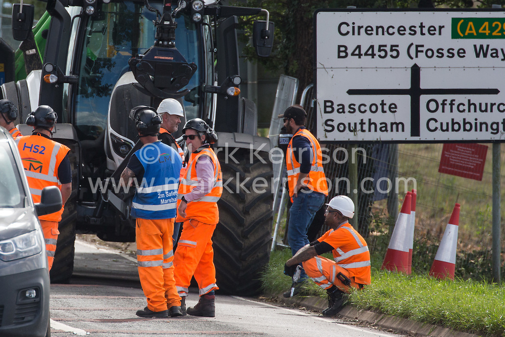 Offchurch, UK. 24th August, 2020. HS2 workers are unable to work because anti-HS2 activists occupied three mature oak trees and a trailer used for transporting wood chip during tree felling works alongside the Fosse Way in connection with the HS2 high-speed rail link. The controversial HS2 infrastructure project is currently expected to cost £106bn and will destroy or significantly impact many irreplaceable natural habitats, including 108 ancient woodlands.