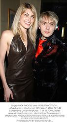 Singer NICK RHODES and MEREDITH OSTROM,  at a dinner in London on 19th March 2003.PIE 142