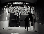 Men look over the gate to a tunnel that leads to the field of a Bull Fighting Stadium in Madrid, Spain