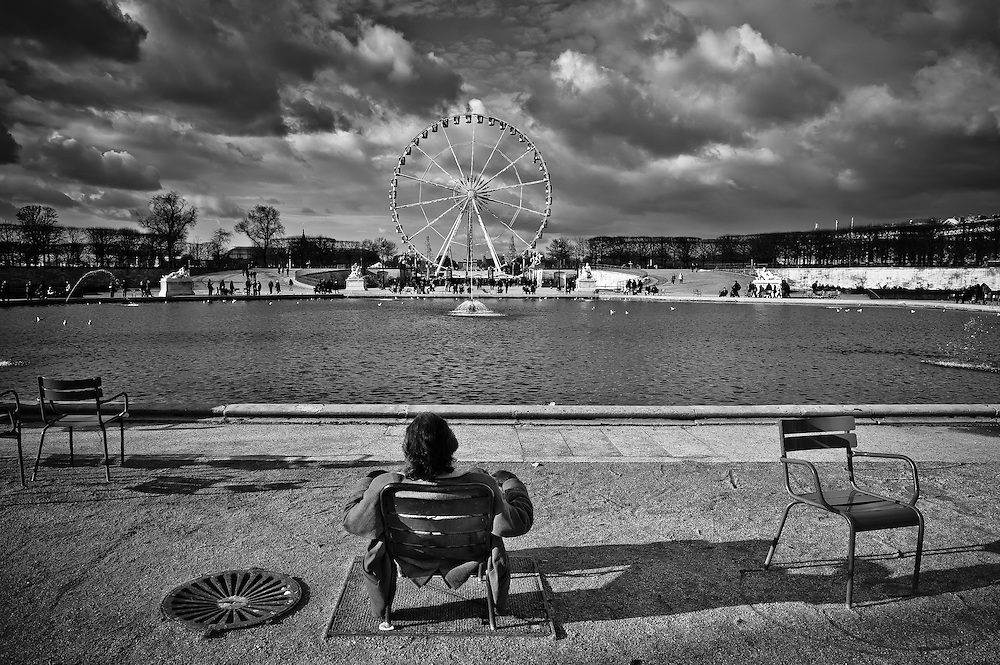 A guy rests on a chair at the Jardin des Tuileries in Paris.