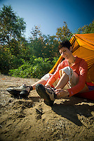 A young woman ties her hiking boots at a campsite in southern California.