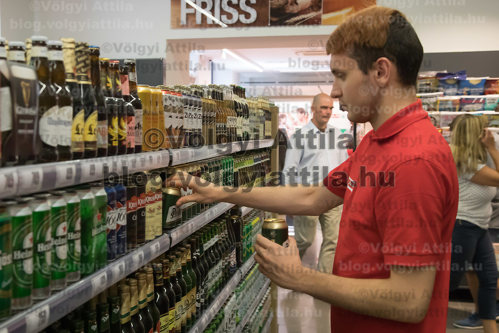 Salesman adjusts alcoholic drink products on the selves before the official opening ceremony of a new Spar food shop in downtown Budapest, Hungary on Aug. 22, 2018. ATTILA VOLGYI