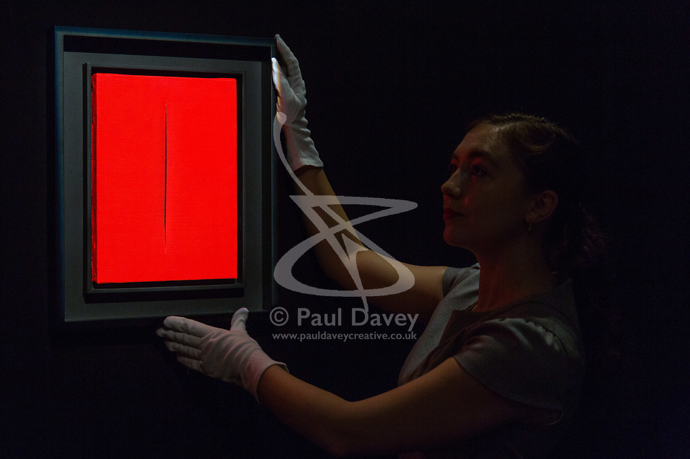 London, September 29 2017. A member of Christie's staff straightens Lucio Fontana' Concetto Spaziale Attesa, estimated to fetch between £400,000-600,000 at auction October 3rd during Frieze Week at Christie's in London. © Paul Davey