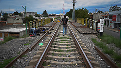 A honduran migrant walks the rail tracks on his way to stow away between carriages on a freight train known to many as La Bestia. Apizaco, Mexico.