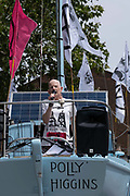 A female campaigner speaking onboard a large blue boat, named the Polly Higgins, used by Extinction Rebellion at The Cut, Waterloo, during a week of climate change actions across the country on the 17th July 2019 in London in the United Kingdom. Extinction Rebellion are a socio-political movement using civil disobedience and nonviolent resistance to protest against climate breakdown, biodiversity loss, and the risk of social and ecological collapse.