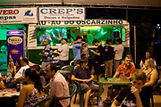 Families and local youths young people sitting, eating and drinking outside a burger vam food stall fast food. Reponte da Cancao music festival and song competition in Sao Lorenzo do Sul, RIo Grande do Sul, Brazil.