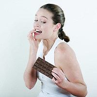 studio portrait on isolated background of a young beautiful caucasian woman holding a chocolate tablet