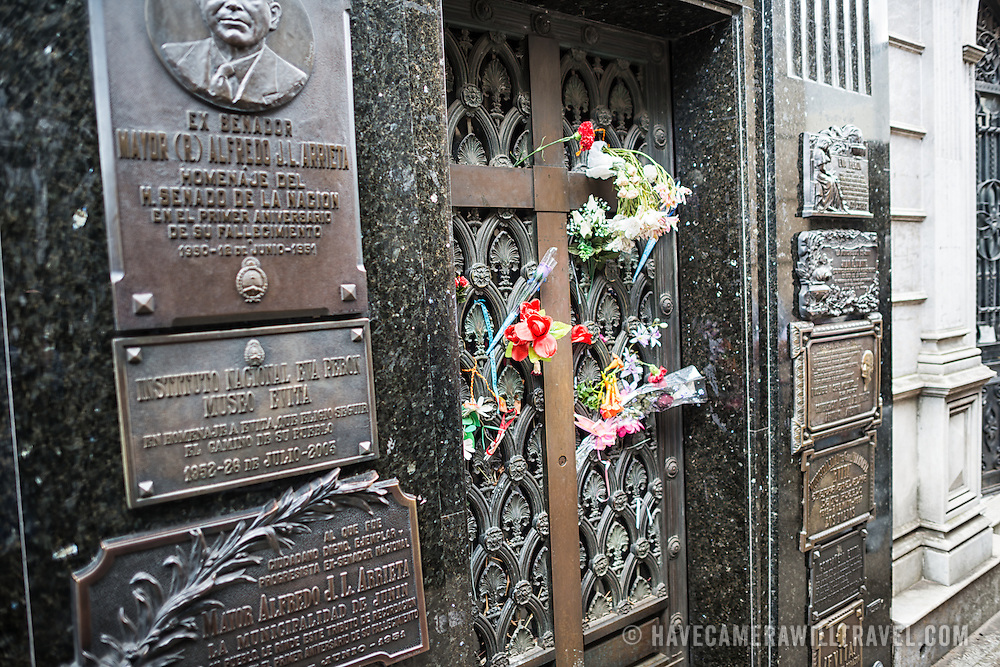 Flowers left by visitors adorn the gravesite of Eva Peron, a former first lady of Argentina and beloved national figure. La Recoleta Cemetery is a famous cemetery in the Recoleta neighborhood of Buenos Aires and is famous for being the burial sites of Eva Peron, Argentinian presidents, and other notables. The cemetery features above-ground gravesites and crypts and is organized into a series of streets and boulevards.