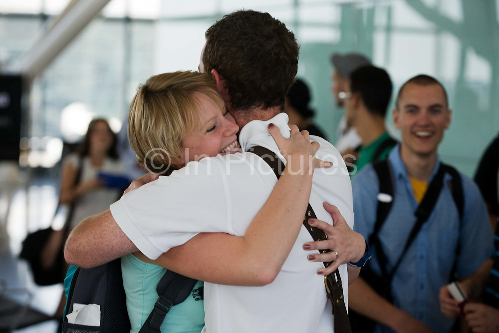 """Honeymooners cuddle in front of other passengers before their round-the-world adventure, leaving from Heathrow Airport's Terminal 5B. The couple are seen embracing at the departure gate as the remaining air travellers filter through the last security checks and board their long-haul flight. The young lady has a look of contentment on her face, the look of happiness and comfort in the arms of her new husband and they hug with all the affection of young love and trust. Another passenger grins in their direction during this show of devotion. From writer Alain de Botton's book project """"A Week at the Airport: A Heathrow Diary"""" (2009). ."""