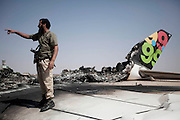Sco0033837 .  Daily Telegraph..A rebel fighter stands on the burnt out hulk of a Libyan Afriqiyah Airlines jet destroyed in the battle for Tripoli airport..Tripoli 28 August 2011. ............Not Getty.Not Reuters.Not AP.Not Reuters.Not PA