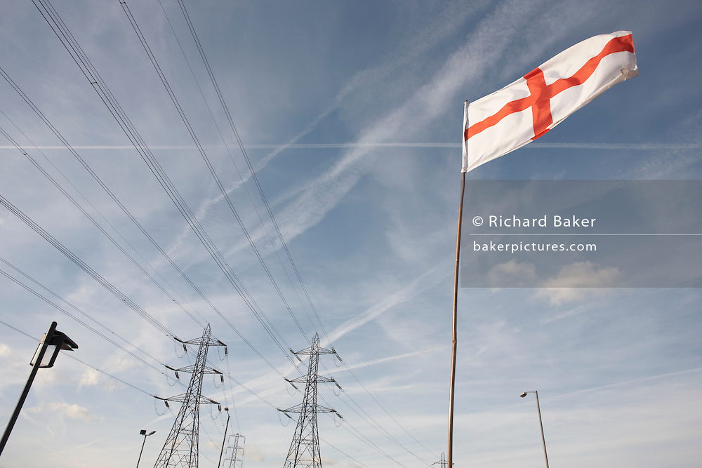 An English Cross of St. George flag flaps in a strong breeze on a flag pole near electricity pylons in Grays,  Thames Gateway