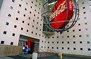 Visitors enter the Coca-Cola corporate museum in the company's Atlanta headquarters. Beneath a giant corporate sign encased in a spherical design, the family of parents and young children enter the building near the 1996 Olympic stadium. Small square windows allow small amounts of light into this museum, a tribute and celebration to this American fizzy drink known around the world. Originally intended as a patent medicine when Atlanta and Fulton County passed prohibition legislation in 1886, John Pemberton responded by developing Coca-Cola, essentially a non-alcoholic version of French Wine Coca. The first sales were at Jacob's Pharmacy in Atlanta, Georgia, on May 8, 1886.