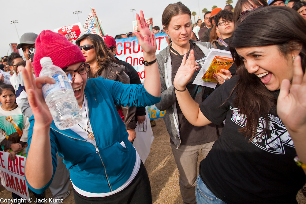 """16 JANUARY 2010 -- PHOENIX, AZ: Romina Memoli (CQ) left, and Angelica Medina (CQ), both from Los Angeles, protest against Sheriff Joe Arpaio in Falcon Park. About 10,000 people marched the 2.5 miles from Falcon Park to the """"Tent City"""" on Durango to protest against Maricopa County Sheriff Joe Arpaio and his immigration enforcement tactics.    PHOTO BY JACK KURTZ"""