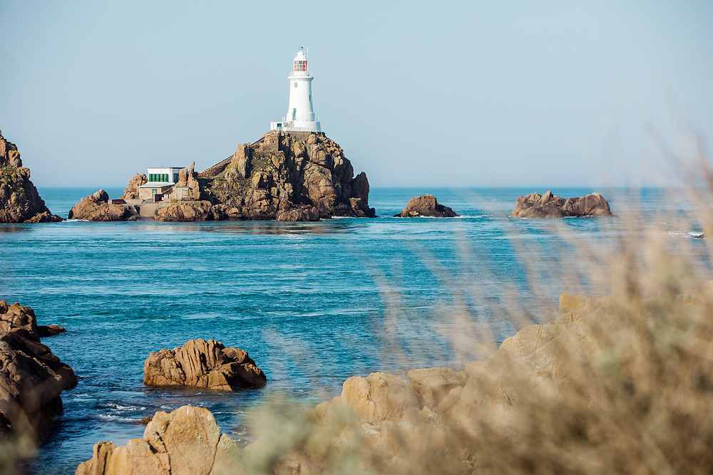 View across the rocks and calm blue sea of Corbiere lighthouse, the popular tourist attraction and landmark in Jersey, Channel Islands in summer