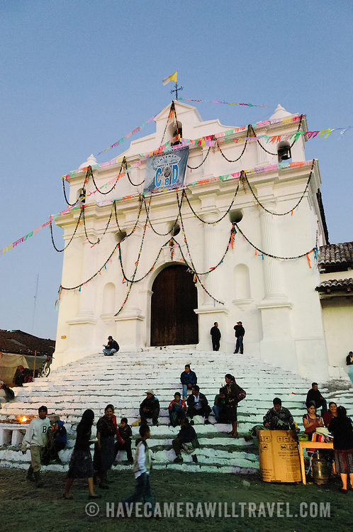 People start gathering in front of the steps of Igelsia de Santo Tomas. The eighteen steps in front of the church signify one for each month of the Mayan calendar. The church is unusual in that it serves as both a Catholic and Mayan religious site, with both religions sharing the space. Chichicastenango is an indigenous Maya town in the Guatemalan highlands about 90 miles northwest of Guatemala City and at an elevation of nearly 6,500 feet. It is most famous for its markets on Sundays and Thursdays.