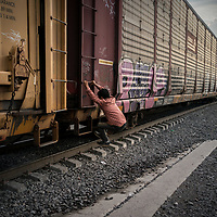 A honduran migrant jumps onto 'La Bestia' a train that is part of a freight network through Mexico. If he is successful the journey will take him more than a month and the most who take the journey experience one or more of the many dangers on the journey, such as being kidnapped and extorted, robbed and beaten, raped, being victims of accidents on the train network, extreme dehydration and even death in the desert, drowning in the rivers to cross into the US.