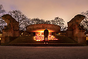 """A person watches candles at  a makeshift memorial in Berlin, Germany, January 17,  2021. The memorial is part of the initiative  """"Corona-Tote sichtbar machen"""" (lit. Make corona deaths visible) by Christian Y. Schmidt and Veronika Radulovic,  since December 6, 2020, people gather at the fountain of Arnswalder Platz every Sunday at 16:00, light candles and place placards with the current death toll reported in Germany at the time. The death toll in Germany by variouse sources revolved around 47,000."""