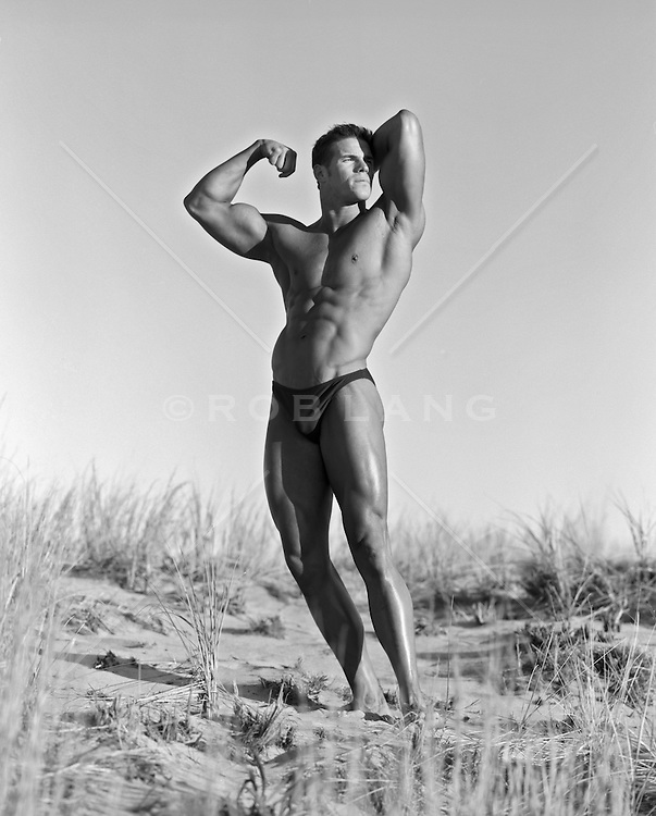 male bodybuilder posing on a sand dune