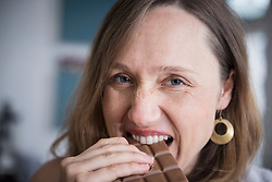 Portrait of a pregnant woman eating chocolate in the kitchen, Munich, Bavaria, Germany
