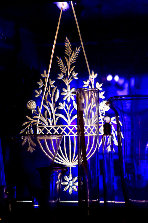 Image of an etched glass hanging flower pot that glows gold with a dark blue background in New Orleans Pharmacy Museum. Two tall crystal vases, one martini glass shaped crystal and one short crystal glass partially obstruct view of the flower pot design.