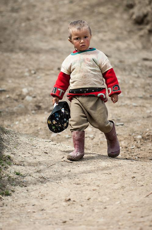 Portrait of an inquisitive village boy walking down a hill in western Tajikistan