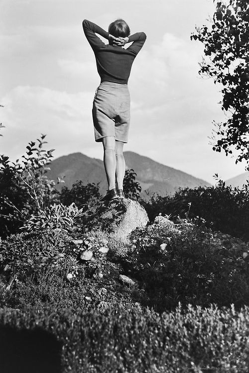 Scene by the house. Woman on the ladder picking apples from the tree and passing them to a woman at the window on the second floor, Austria, 1934