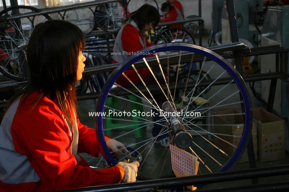 China, Beijing, Bicycle factory making a wheel