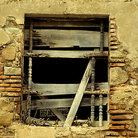 Central America, Guatemala, Antigua. A dilapidated window with makeshift shutters in Antigua, Guatemala.