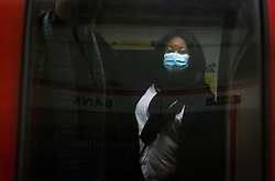 © Licensed to London News Pictures. 16/03/2020. London, UK. A woman wearing a face mask looks out from an underground train at Bank Station in the City of London this morning. New cases and fatalities resulting from the COVID-19 strain of the Coronavirus continue to be reported daily in the UK with major sporting fixtures cancelled and people advised to stay at home if they have a cough and high temperature. Photo credit: Vickie Flores/LNP