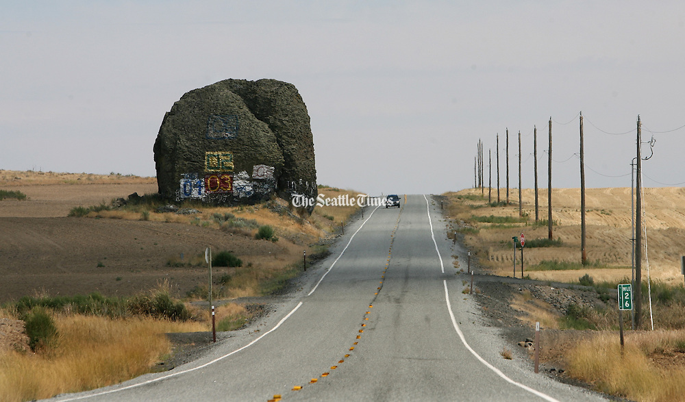 A giant boulder left from Ice Age floods still sits along Highway 172 near the town of Mansfield, a few miles from Steamboat Rock. (Steve Ringman / The Seattle Times)