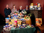 (MODEL RELEASED IMAGE). The Bainton family in the dining area of their living room in Collingbourne Ducis, Wiltshire, with a week's worth of food. Left to right: Mark Bainton, Deb Bainton, (petting Polo the dog), and sons Josh, and Tadd.  The Bainton family is one of the thirty families featured in the book Hungry Planet: What the World Eats (p. 140).
