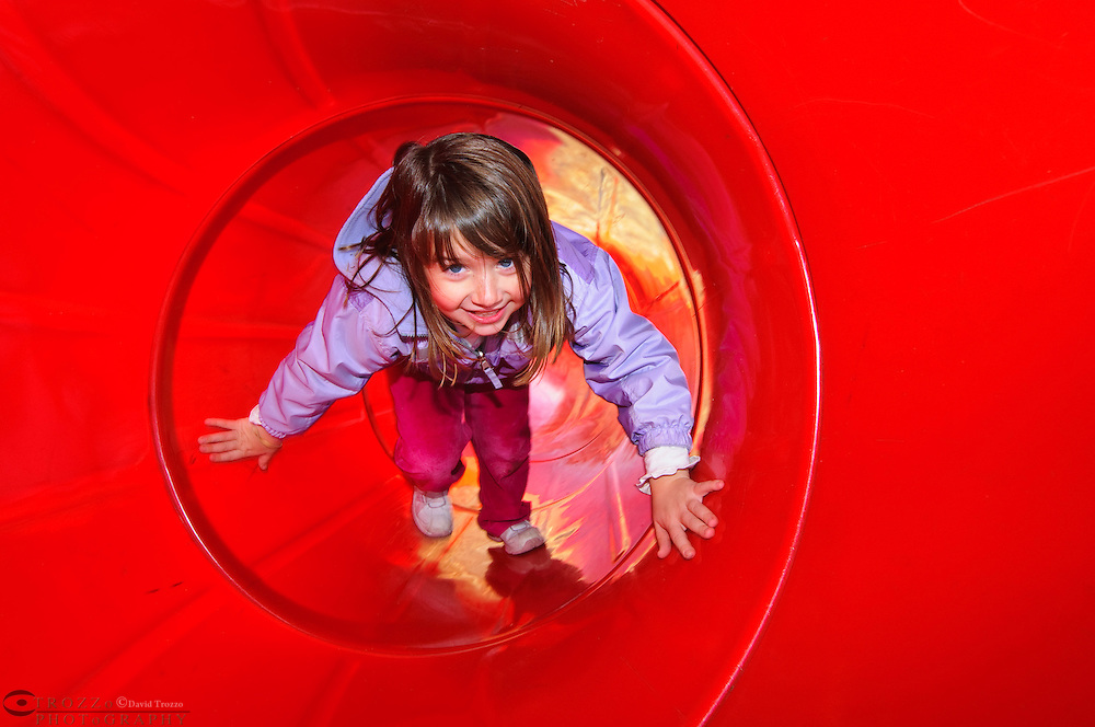 Little girl playing on a tube slide on a playground.