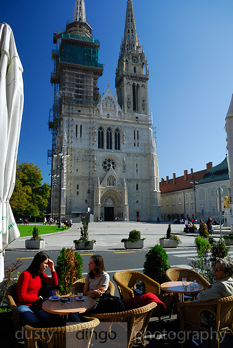 People sitting in outdoor sidewalk cafe, Cathedral of the Assumption of the Blessed Virgin Mary and Saint Stephen (Sveti Stjepan) in background. Zagreb, Croatia