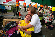 12 local activists locked themselves in specially made arm tubes to block the entrance to Quadrillas drill site in New Preston Road, July 03 2017, Lancashire, United Kingdom. An exhausted Alana McCullogh has released herself from her armlock after 15 hours and is looked after by a friend.  The 13 activists included 3 councillors; Julie Brickles, Miranda Cox and Gina Dowding and Nick Danby, Martin Porter, Jeanette Porter,  Michelle Martin, Louise Robinson,<br /> Alana McCullough, Nick Sheldrick, Cath Robinson, Barbara Cookson, Dan Huxley-Blyth. The blockade is a repsonse to the emmidiate drilling for shale gas, fracking, by the fracking company Quadrilla. Lancashire voted against permitting fracking but was over ruled by the conservative central Government. All the activists have been active in the struggle against fracking for years but this is their first direct action of peacefull protesting. Fracking is a highly contested way of extracting gas, it is risky to extract and damaging to the environment and is banned in parts of Europe . Lancashire has in the past experienced earth quakes blamed on fracking.