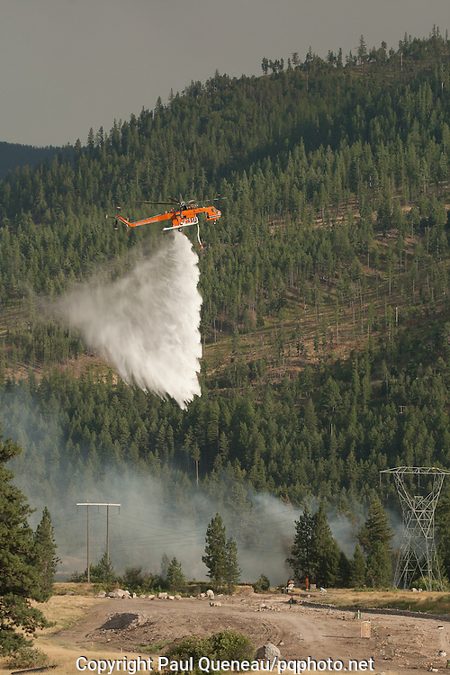 An Erickson Air-Crane showers part of the Clark Fork onto a small wildfire in East Missoula.